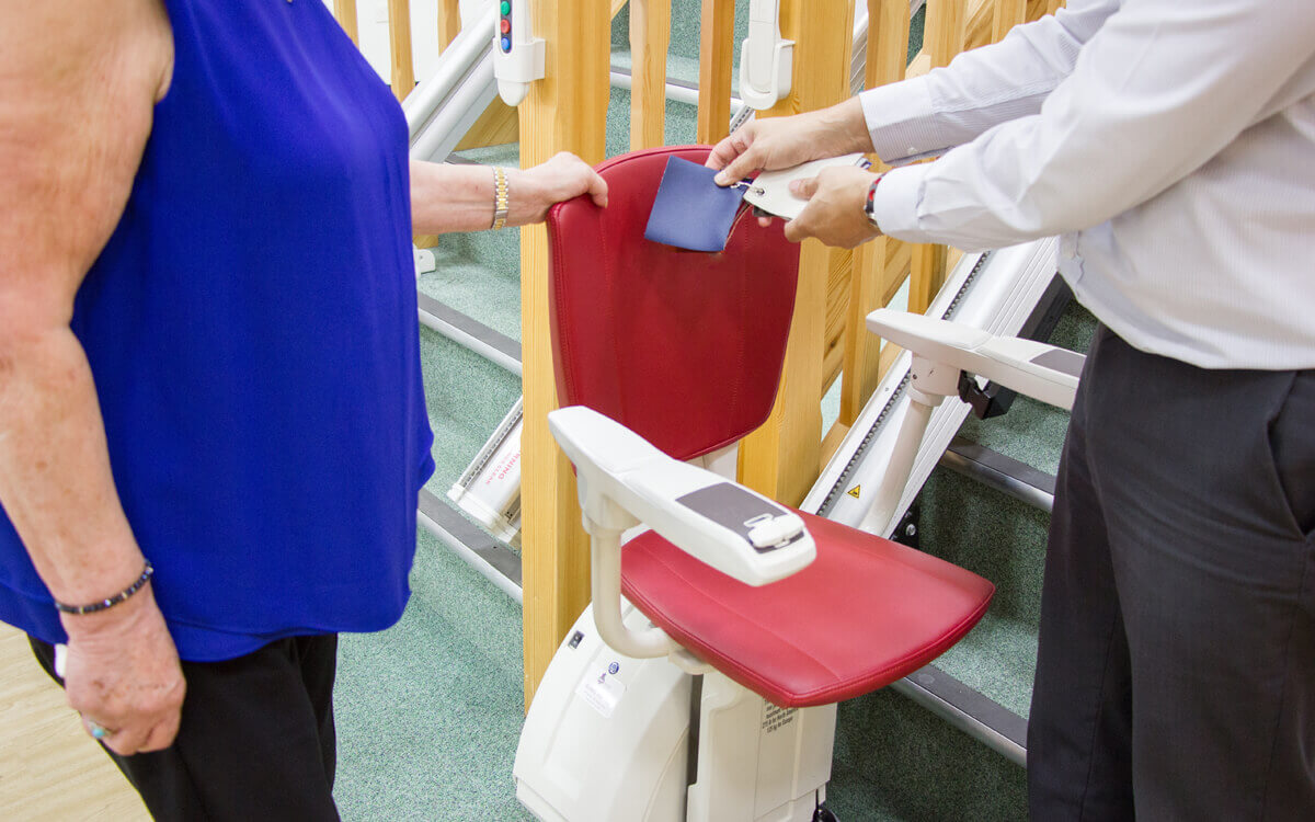 Two people looking at a stairlift