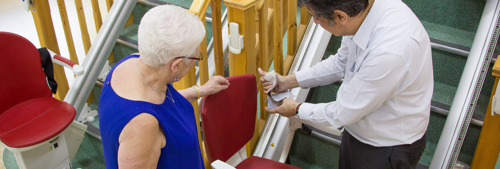 elderly lady being shown a stairlift by an advisor