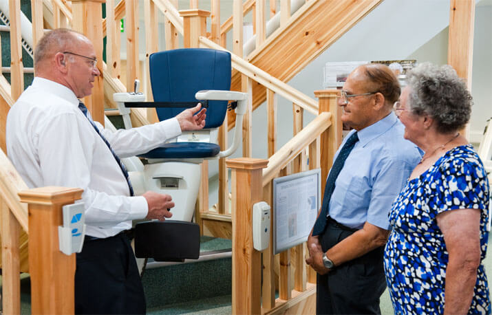 Stairlfit Advisor Guiding Elderly Customers in Showroom