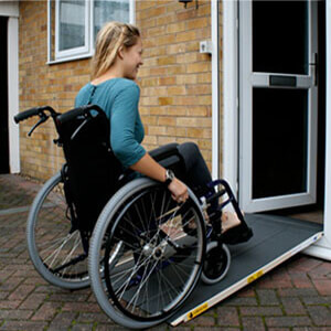 A young lady in a wheelchair using a ramp into a house