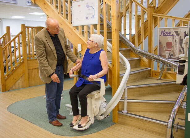 a woman being advised on a stairlift by an advisor in a stairlift showroom